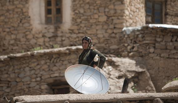 На иллюстрации: Иранка со спутниковой антенной на крыше своего дома.